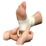 first aid attendant bandaging foot